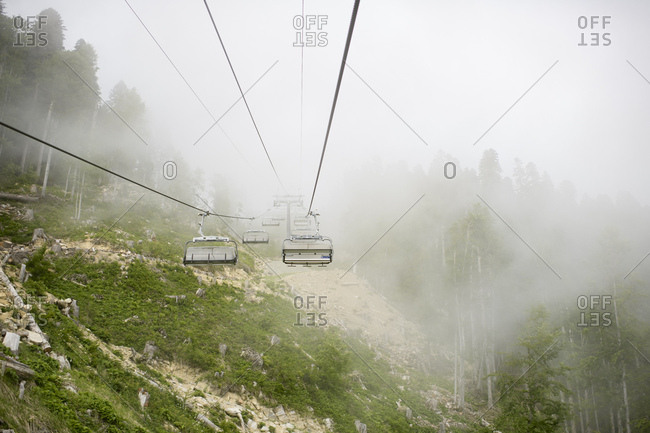 Russia- Sochi- empty cable railway in cloudy forest