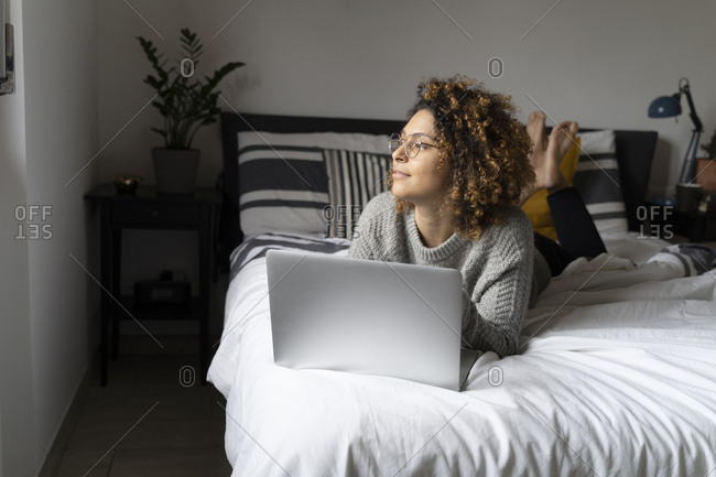 Woman lying on bed- using laptop- surfing the net
