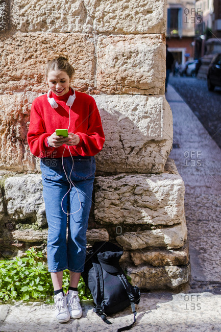 Young woman wearing red pullover- using smartphone in Verona