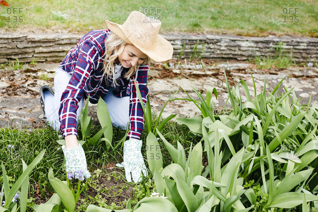 Young woman with a straw hat weeding weeds