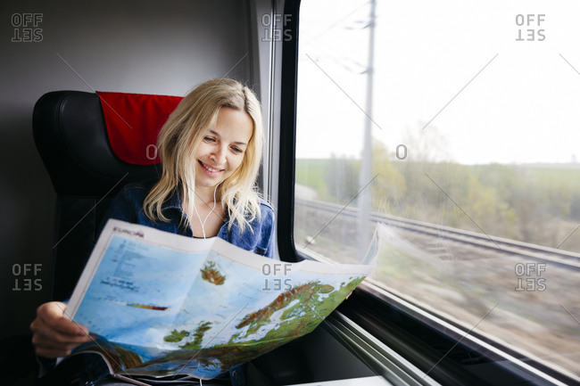 Portrait of happy blond woman travelling by train looking at map of Europe