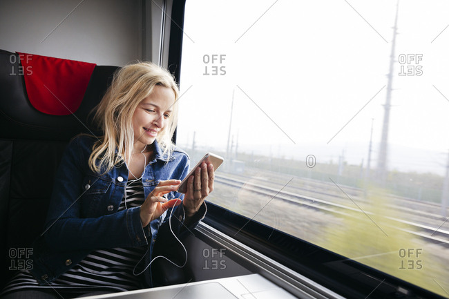Smiling blond woman travelling by train using smartphone and earphones