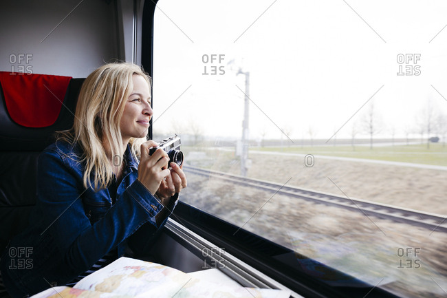 Happy blond woman with camera travelling by train looking out of window