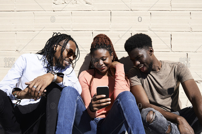 Three friends sitting together and watching a video on a smartphone outdoors
