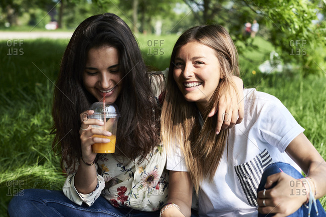 Portrait of two happy young women drinking juice at a picnic in park