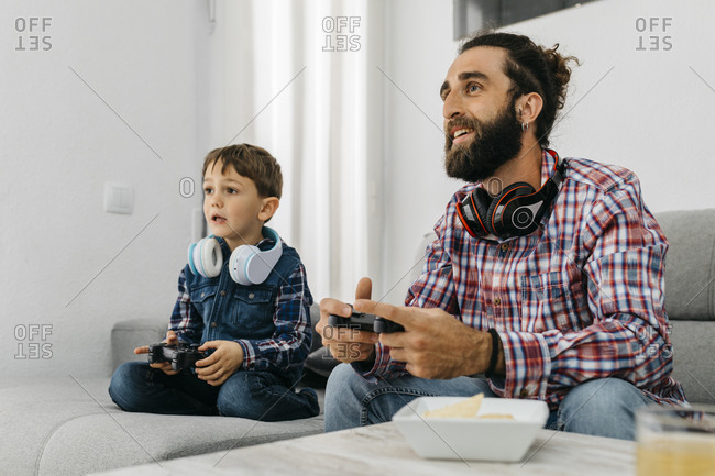 Portrait of father and son sitting together on the couch playing computer game