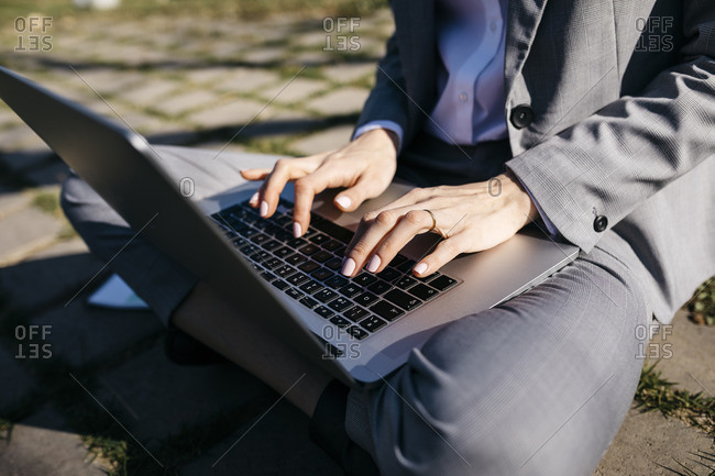 Businesswoman in the city- sitting on ground- working on laptop