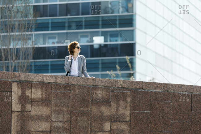 Successful young businesswoman standing at wall in front of office building