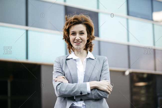 Portrait of a successful young businesswoman in the city- with hands in pockets