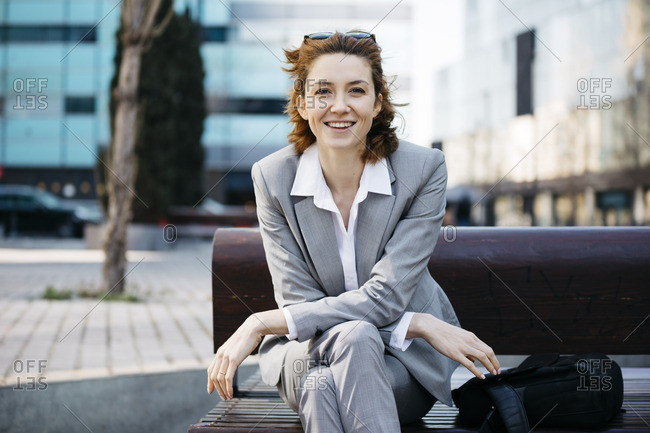 Young confident businesswoman sitting on a bench in the city- looking at camera