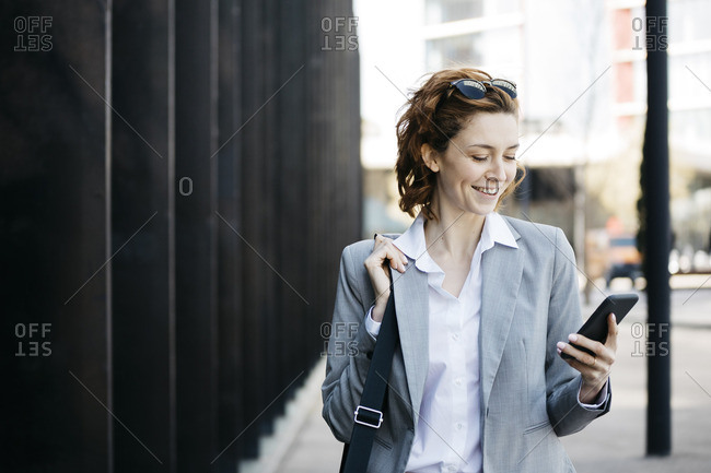 Businesswoman with smartphone- commuting in the city