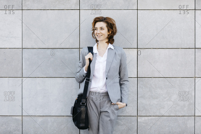 Portrait of a young confident businesswoman in front of wall with gray tiles