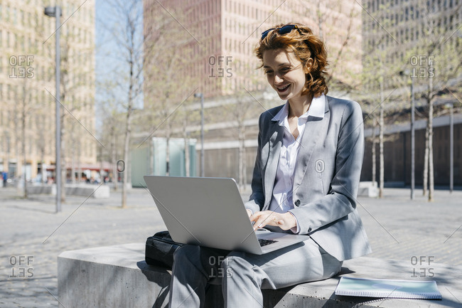 Young businesswoman with red shoes- sitting on a bench in the city- working on laptop