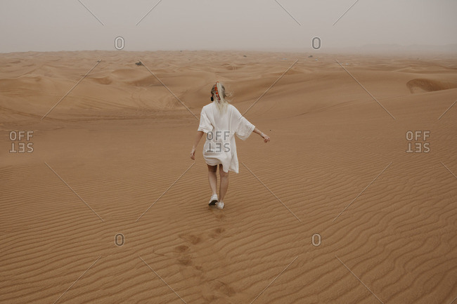 United Arab Emirates- Dubai- Lahbab Desert- woman walking in desert landscape