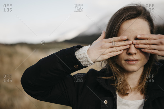 UK- Scotland- young woman covering her eyes in rural landscape