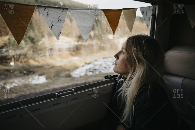 Pensive young woman looking out of car window