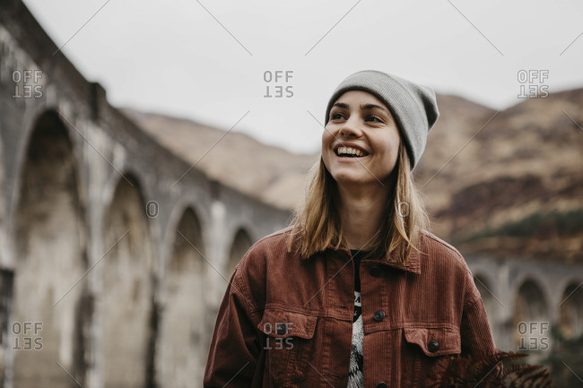 UK- Scotland- Highland- portrait of happy young woman at Glenfinnan Viaduct