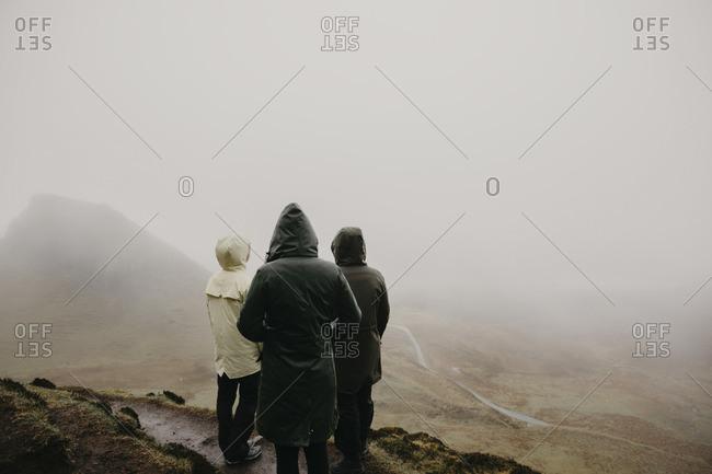 UK- Scotland- Isle of Skye- Quiraing Viewpoint- rear view of three women in foggy landscape
