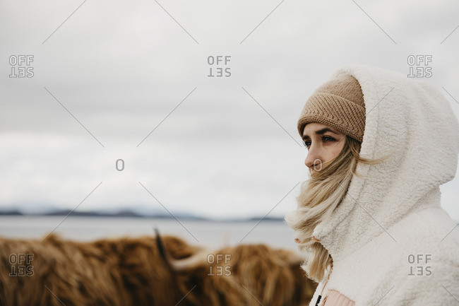 UK- Scotland- Highland- young woman and longhorn cattle on pasture