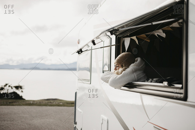 UK- Scotland- Highland- young woman at the window of a camper van