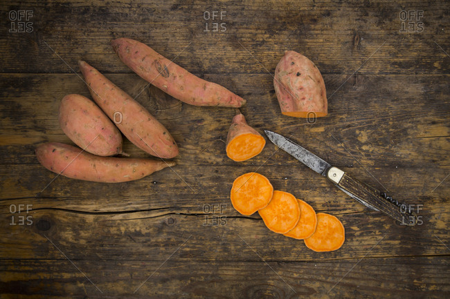 Sliced and whole sweet potatoes on dark wood