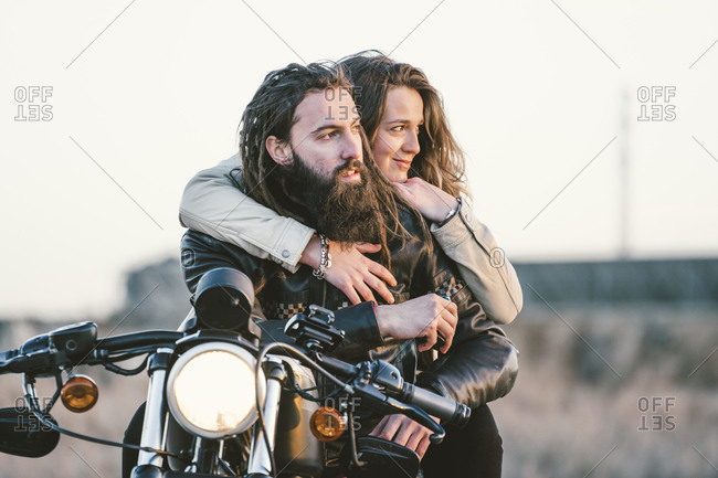 Portrait of couple on motorbike looking at distance