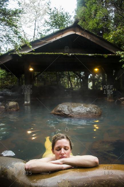Japan- Kyushu- woman enjoying hot springs