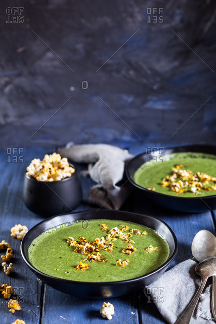 Vegan green vegetable soup with spinach- leek and peas- chili popcorn