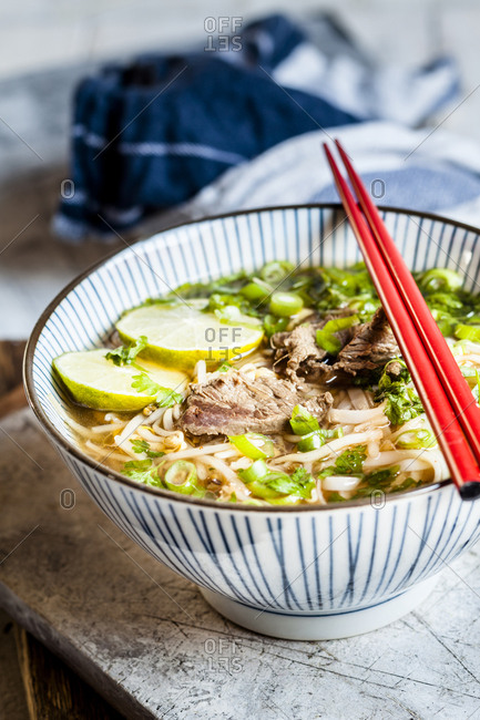 Bowl of Vietnamese Pho with rice noodles- mung beans- cilantro- spring onions and limes