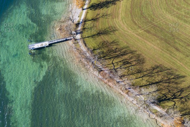 Germany- Bavaria- Kaltenbrunn- Tegernsee- shadows of trees at the lakeshore and jetty- aerial view