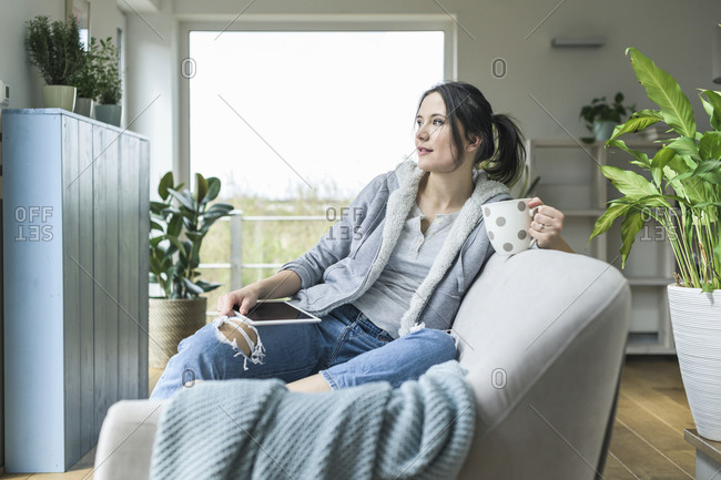 Pensive woman with a mug and tablet sitting on the couch at home