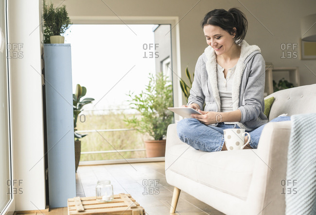 Woman with a mug sitting on the couch at home using tablet