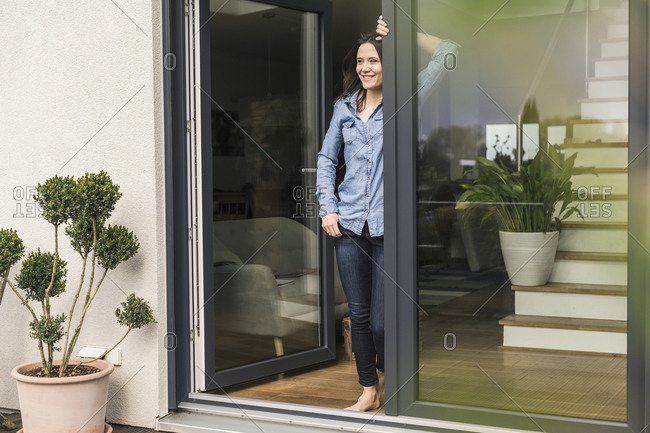 Smiling woman standing at terrace door at home