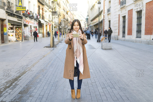 Spain- Madrid- young woman taking photos with a smartphone in the city