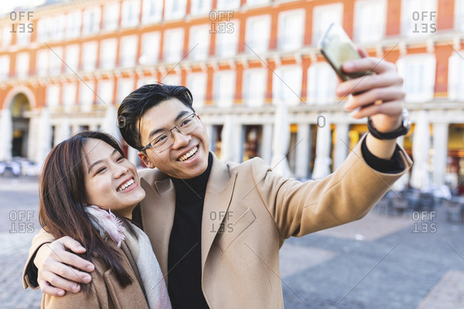 Spain- Madrid- happy young couple taking a selfie in the city