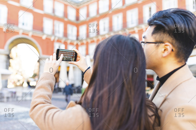 Spain- Madrid- young couple taking a smartphone picture in the city