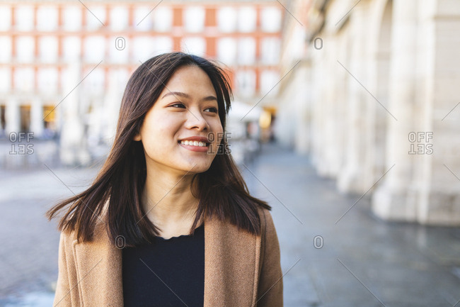 Spain- Madrid- portrait of smiling young woman at Plaza Mayor
