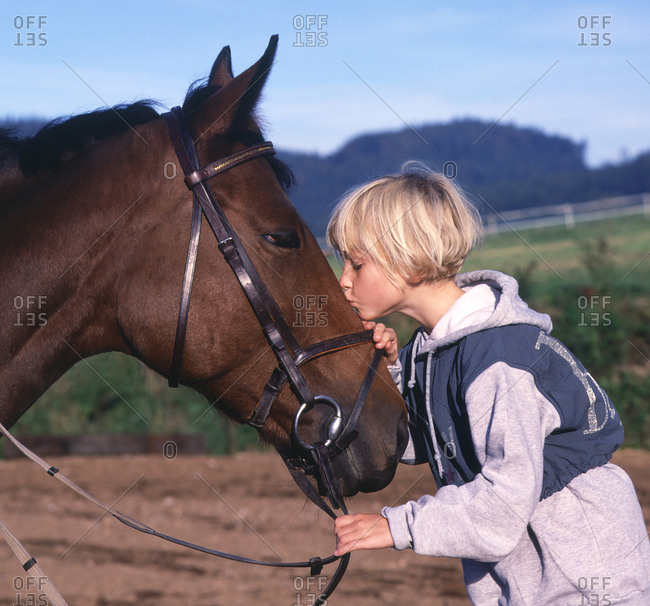 Girl kissing a horse affectionately