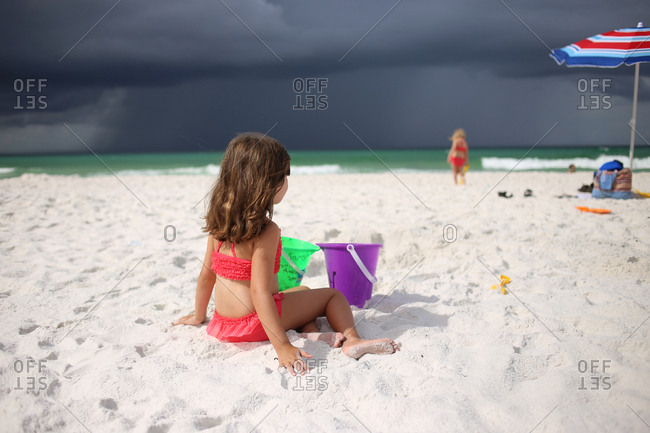 girls at the beach with stormy skies