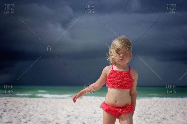 girl at the beach with dark skies