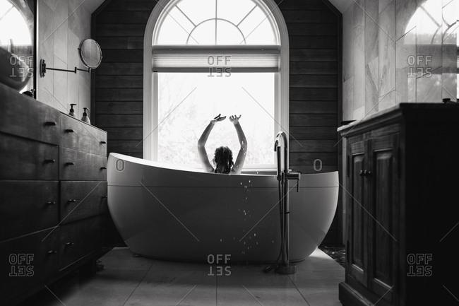 girl making a splash in the tub