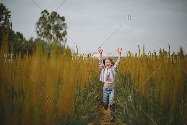 A girl  smiling while running in Aromerus flowers field