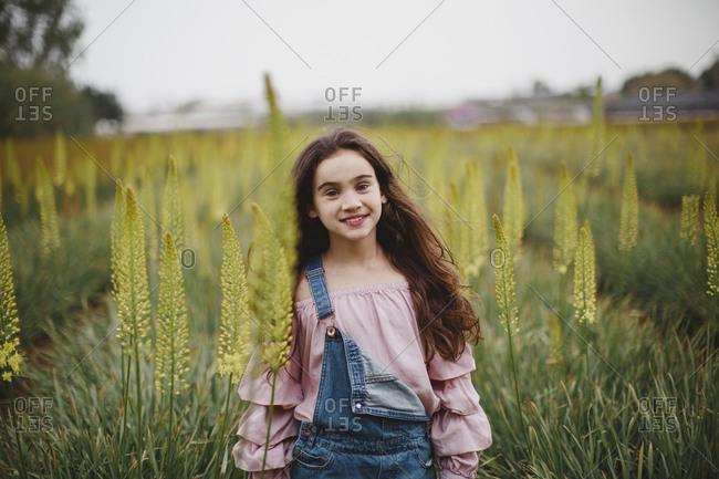 A girl standing in Aromerus flowers field
