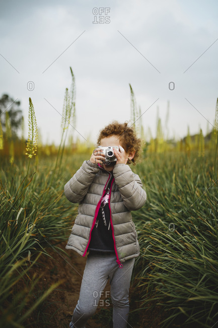 A girl standing in Aromerus flowers field holding a camera