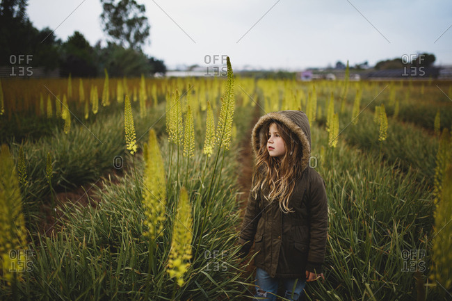A girl in a coat standing in Aromerus flowers field