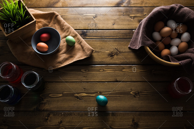 Overhead shot of a bunch of colored easter eggs and jars of dye on a wooden table.