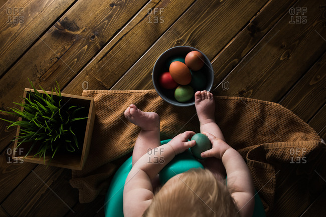 Overhead shot of a baby holding a colored easter egg on a wooden table.