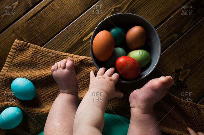 Shot of a baby's feet and hands reaching for colored easter eggs.