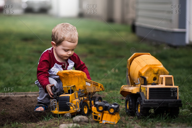Young boy playing with toy trucks in the grass.