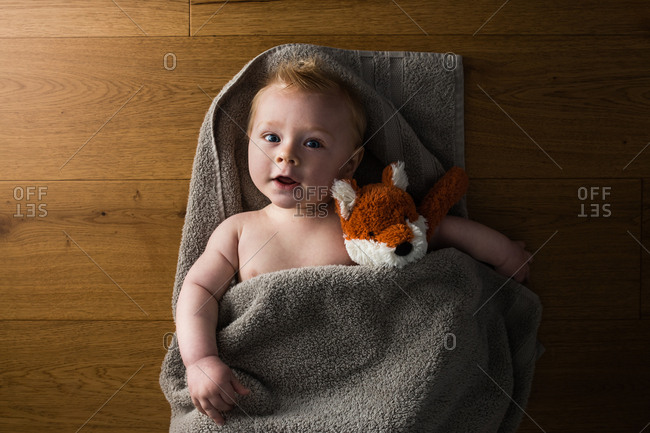 Young kid wrapped in a towel with a stuffed fox.